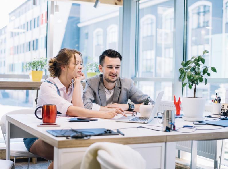 Une femme et un homme qui travaillent ensemble sur PC